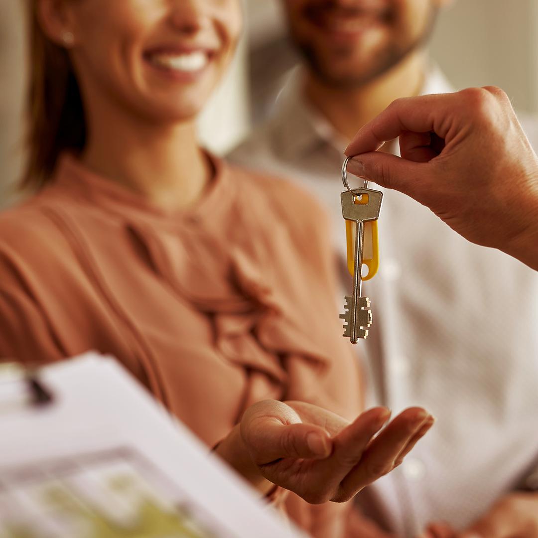 imagem com duas pessoas pegando uma chave que apresenta investimento em imóveis na pandemia